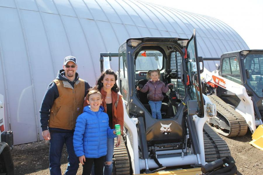 Anthony Dragt (L), new salesman of Farm-Rite Equipment of Willmar, with his family: son Blake, wife Tiffany and daughter Leila getting ready to give this Bobcat T-76 a quick test drive.