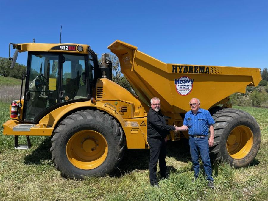 Allan Patterson (L), regional business manager, Hydrema, and Louie Gobbi, owner of G&G Heavy Equipment Rentals, shake hands next to G&G's Hydrema 912HM articulated dump truck.