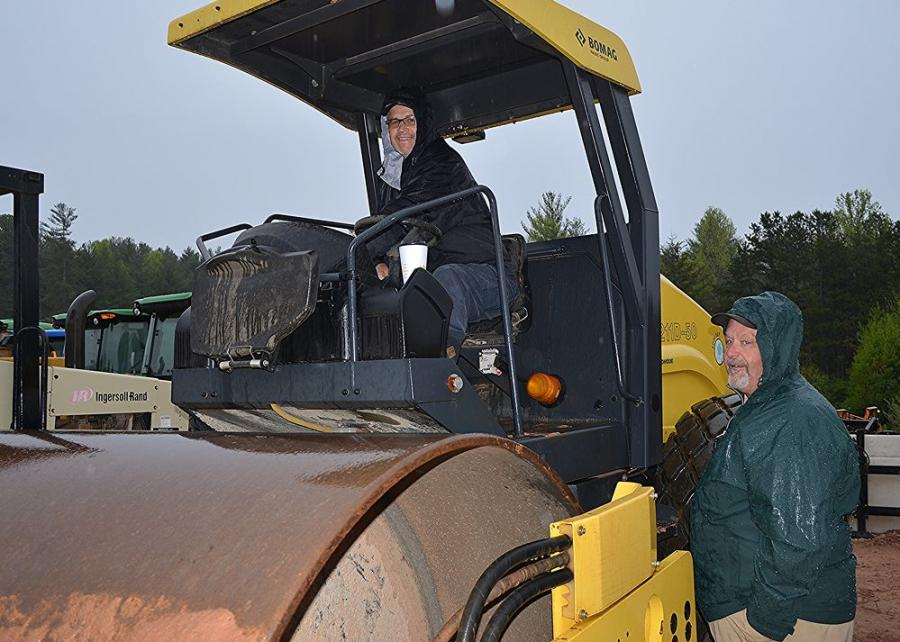 Checking out a Bomag BW 211D compactor while dodging a few raindrops are Doug Saxon (in cab) and Rick Gailey of Chattahoochee Group, Clermont, Ga.