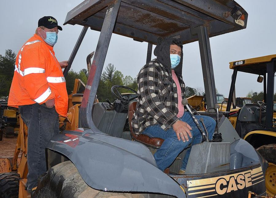 Contractors from Winder, Ga., give a Case 580L backhoe a complete inspection before the auction got under way.