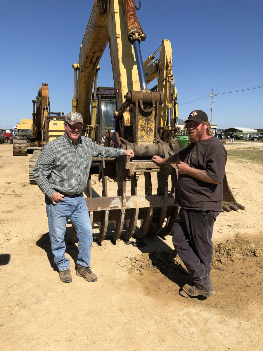 Chris Marion (L) and David Motes, both of Kenny Ring Grading in Carthage, N.C., are looking over the grapple root rake on an excavator.