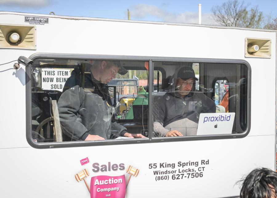 Sam Sales, owner of Sales Auction Company, in the action truck with the Proxibid operator. Proxibid allows for virtual bidding at the live event.