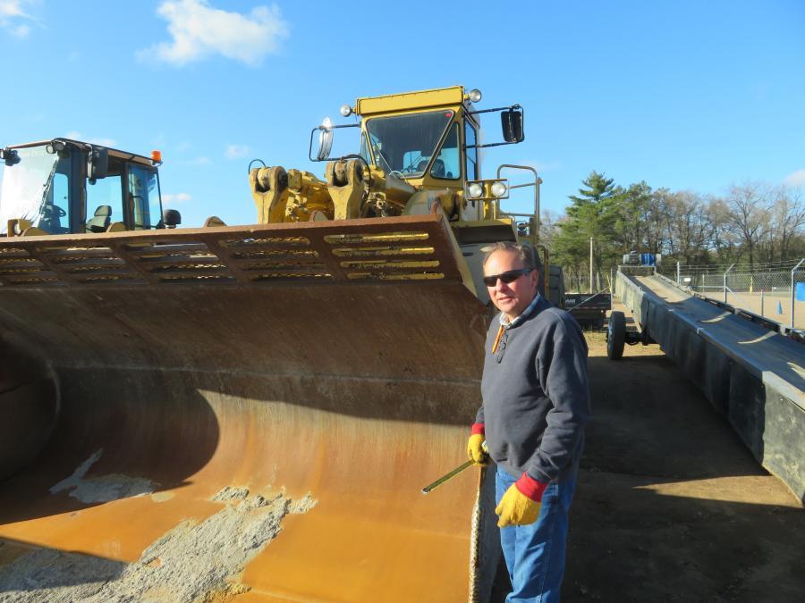 Jeff Hoffman of J. Hoffman Truck & Equipment checks the measurements of the bucket on this Caterpillar 988B wheel loader.