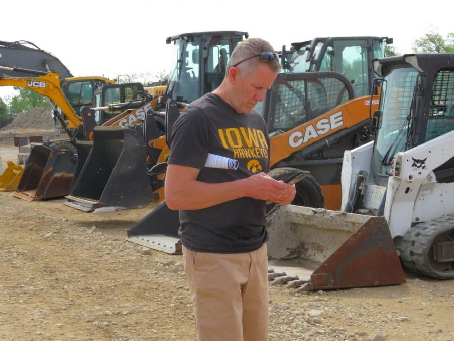 Bud Pecoy, president Mid Country Machinery Inc., checks some messages prior to the start of the auction.