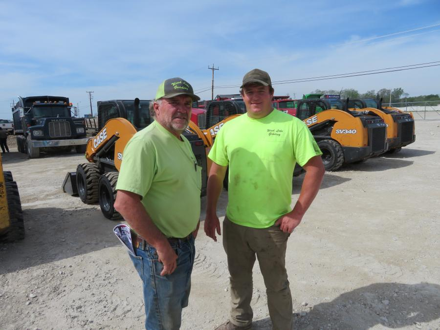 Russ (L) and Jake Bonnert, both of Wind Lake Grading, look over the late-model, low-hour skid steers.