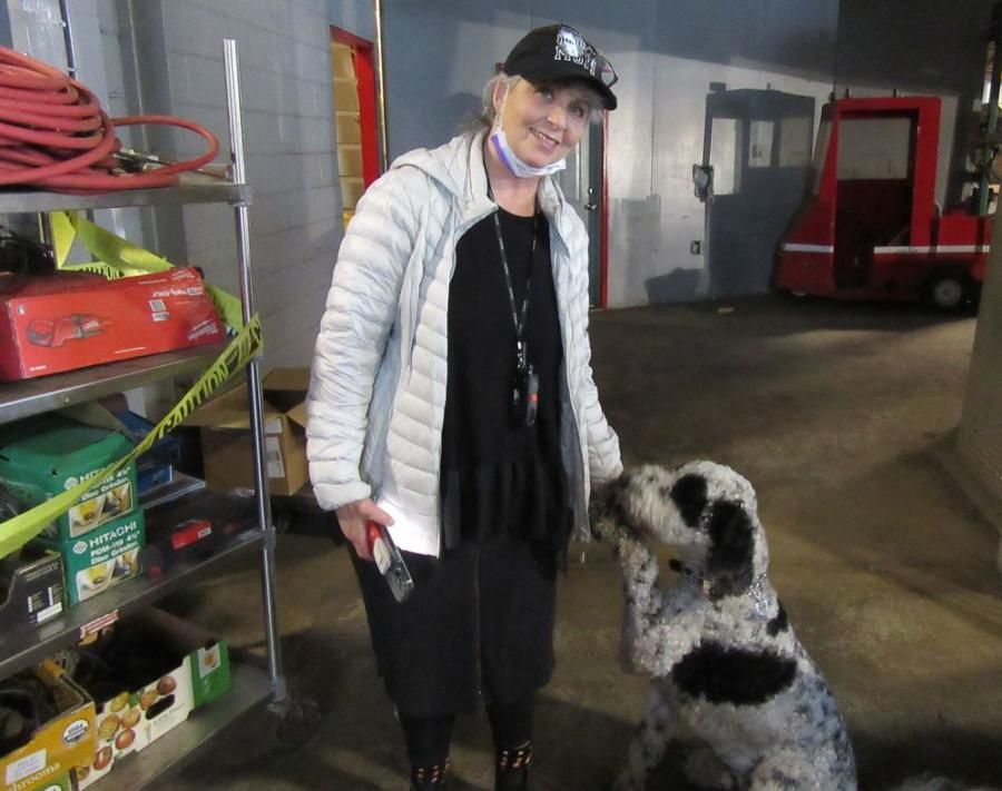 Sheila Rosen, Rosen & Company president, has some help from her canine auction assistant, Goje, to ensure the auction runs smoothly.