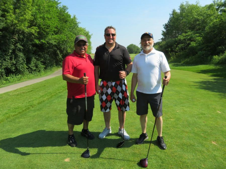 Dave Wawrzyniec of Alta Equipment (C) hits the fairway with Jose Garcia (L) and Enrique Gonzalaz, both of Natural Creations Landscaping Inc.