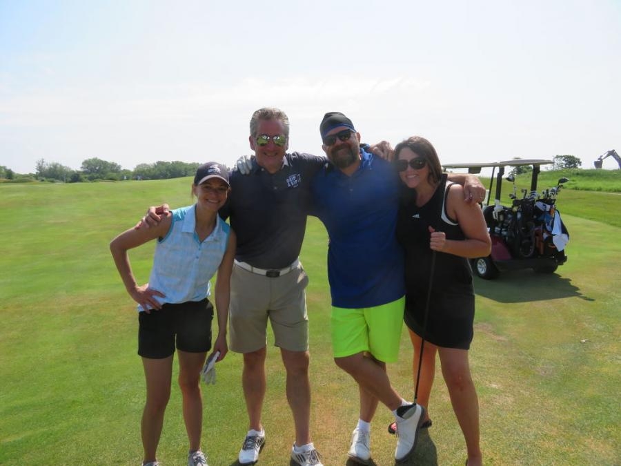 Jennifer Keys (R) of Alta Equipment welcomes (L-R) ESPN's Jessica Taylor, Dave Scharf and Brian Waterkotte to the tournament.