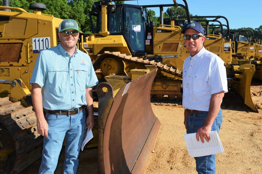 Looking over some of the dozers before sale time are Caleb Phillips (L) and James King of Granite Mountain Machinery, Conyers, Ga.