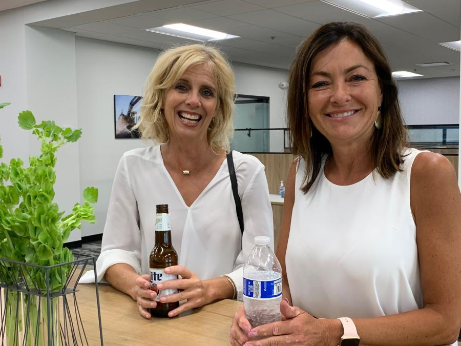 Jane Willey (L) of CoreBuilt Contracting, and Allison Malzone of Stewart Title Guaranty Company, catch up at the WRB gathering at West Side Tractor Sales.