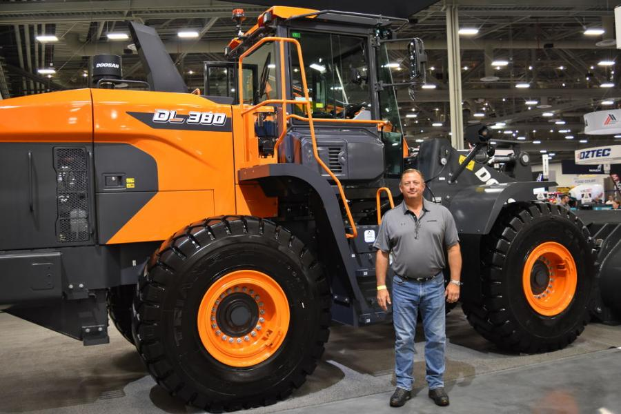 """Bill Zak, wheel Loader product specialist of Doosan, stands in front of the DL 380-7, which features an all new cab, new styling, improved visibility, rear camera and hi/low mounted cameras, which allow for a transparent bucket. Cameras allow the operator to """"see through"""" the bucket."""