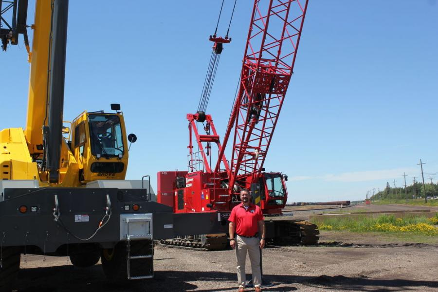 """Colby Bingaman, regional business manager of Manitowoc, Shady Grove, Pa., shows off the Manitowoc and Grove crane lines setup out front. """"This is a great group of people to work with,"""" said Bingaman. """"Hayden-Murphy does a great job of taking care of its customers' needs for any project."""""""