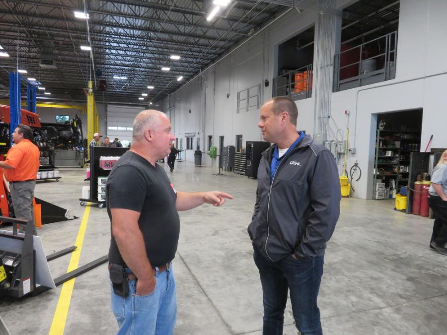 Kevin Ridens (R), director of sales of 1ST Choice Equipment Co., shows the shop area to Chris Wieteska of EC Excavating.