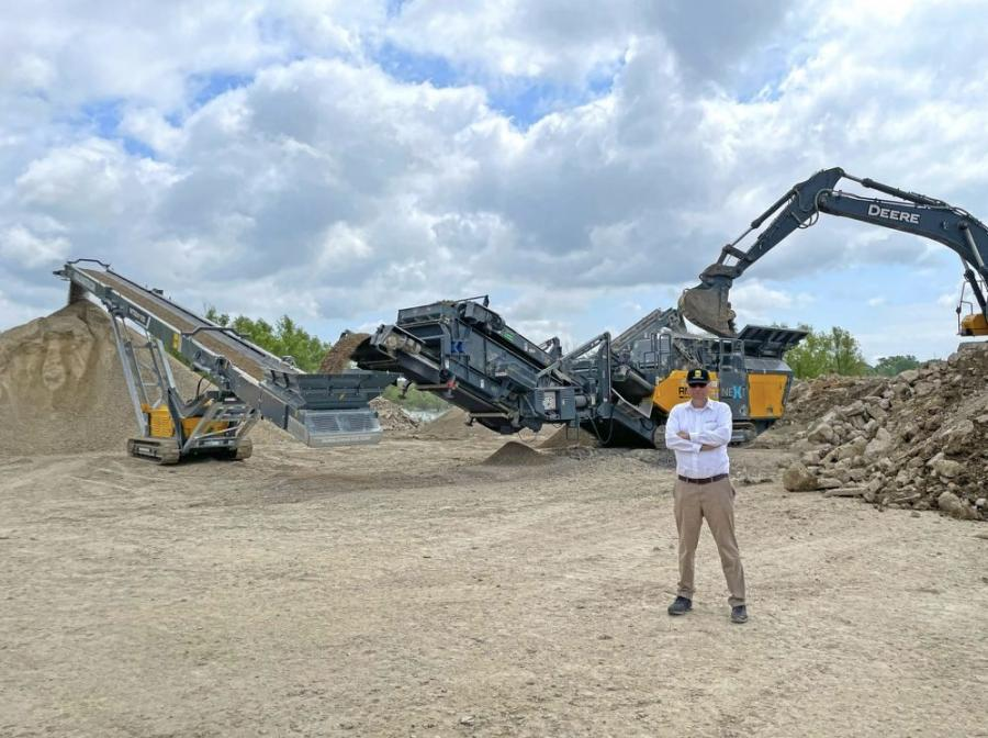 Gerald Hanisch, owner and president of Rubble Master, standing in front of the RM 120X Mobile Impact Crusher producing flexbase and stockpiling the material with the RM MTS2412S 80-ft. tracked conveyor.