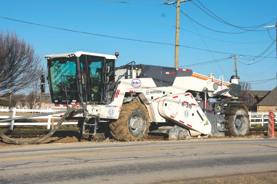 Operator Ian Patterson injects slurry into existing roadway materials with a Wirtgen WR 200 XLi recycler/stabilizer on a job site to expand the intersection of Wagley Robertson Road and Bonds Ranch Road in Fort Worth, Texas.