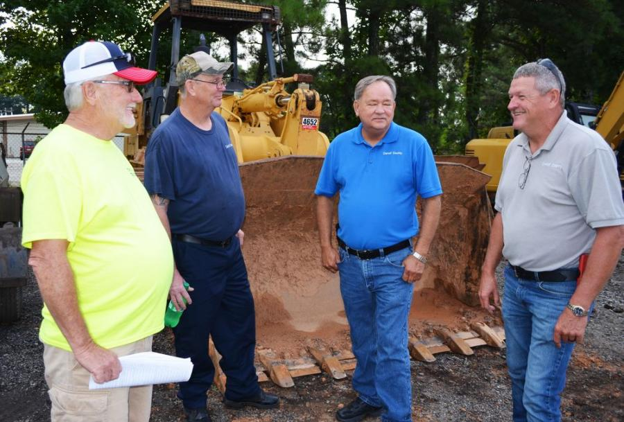 Talking about the machine lineup about to be sold (L-R) are Travis Hill, Travis Hill Trucking, Villa Rica, Ga.; and Lee McGuffin, Charles Pope and Danny Yates of Carroll County Public Works, Carrollton, Ga.