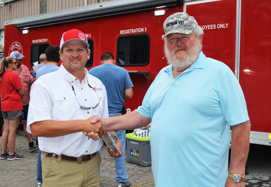 Joey Martin (L) and Larry Jackson share a hearty handshake before the auctioning gets under way and the unofficial last day of business for Jackson Paving in Douglasville.