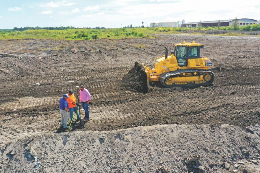 """(L-R) Linder Industrial Machinery Company TSE Eric Moraguez, Downrite Engineering GPS Superintendent Lincoln Dacosta and Linder sales representative Randy Dominguez examine the rover station that communicates with the new Komatsu D71PXi-24 dozer. """"At our County Line Phase Four job site, the machine has cut our grading time in half. The power combined with the integrated 2.0 intelligent Machine Control GPS technology allows us to move large quantities of material and cut the pad to grade without stakes or masts,"""" noted Dacosta."""