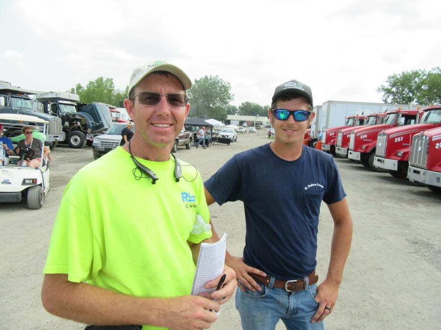Brad Dalton (L) and Bailey Keith of B. Dalton Farms reviewed the dump trucks.