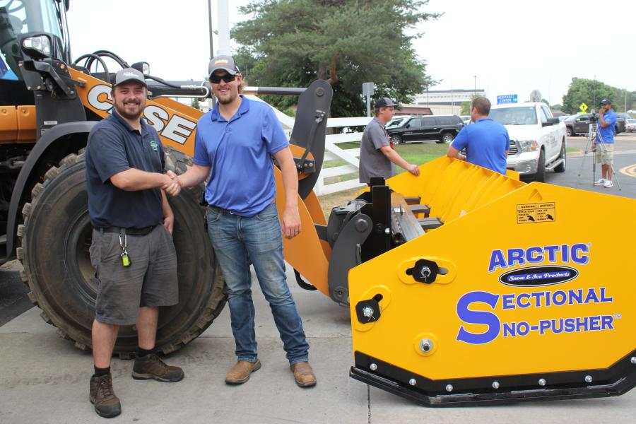 Tyler Parker (L), shop manager of MN LawnPros in Brooklyn Park, Minn., with AJ Kalupa, sales consultant of Titan Machinery Equipment, Rogers, Minn., with a 22-ft. Arctic sectional plow system.