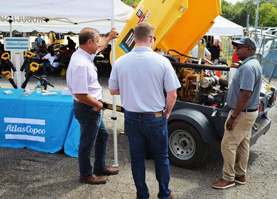 Eudes Defoe (R), of Atlas Copco, talks with some attendees about the Atlas Copco Power Connect app that provides info and tracking for compressors or generators.