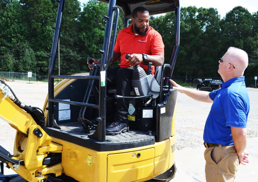 Tennyson Hull (L) of the University of Georgia grounds department gets some instruction on the mini-excavator challenge from Matthew Hyde, Yancey Bros. Co. demo operator.