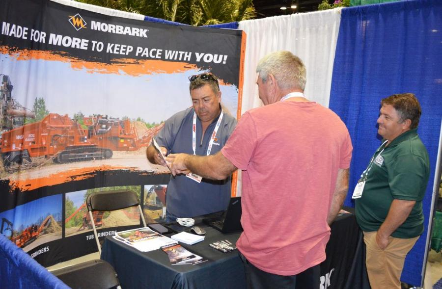 Morbark's International Sales Manager George Perez (L) provides additional info and some quotes to show goers interested in the Morbark line of equipment.