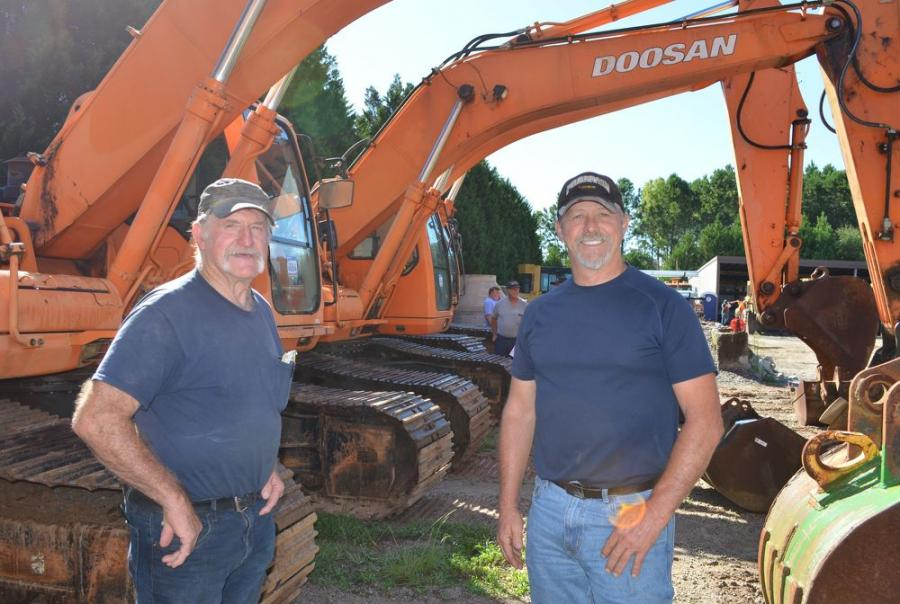 """Looking over some of the """"orange iron"""" about to be auctioned are Jim Fortner (L) and Gary Fortner of Busses at Loganville, a local bus sales company that also does some land clearing."""