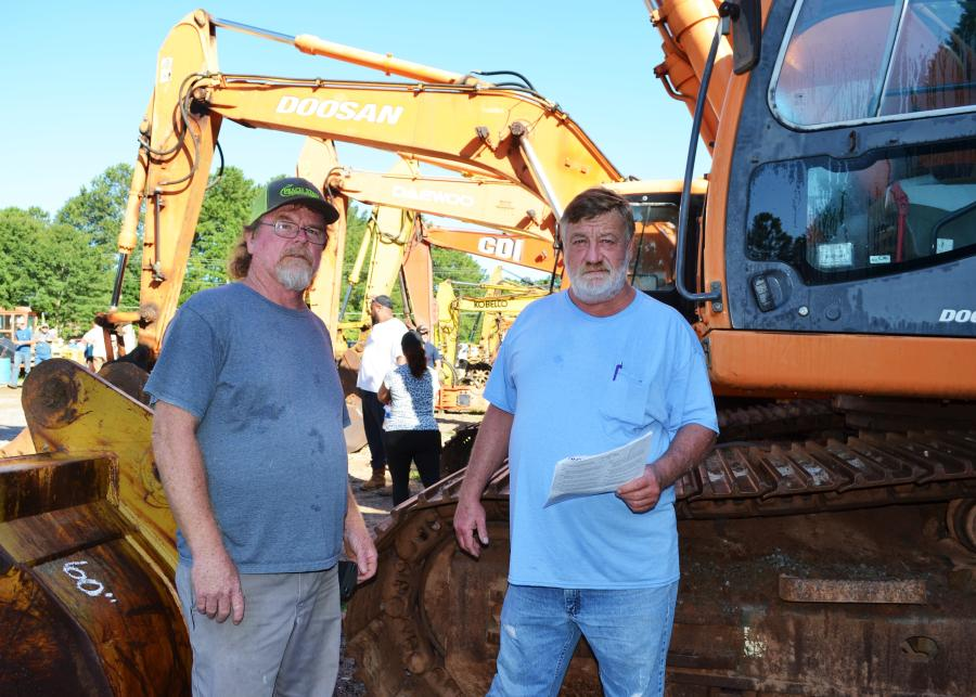 Reading up on some of the equipment being auctioned are Greg Hayes (L) of Hayes Hauling, Conyers, Ga., and Bryan Hayes of B&H Quarries, Elberton, Ga.