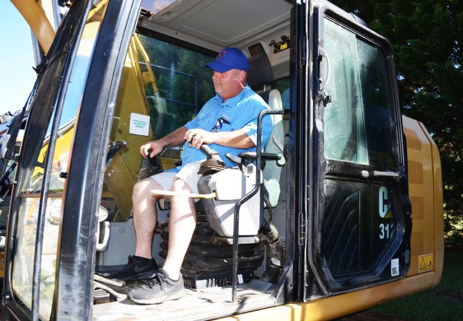 After being top bidder on a lube truck, Brian Yancey of Contour Grading & Pipe, Loganville, Ga., does one more inspection of a Cat 312E of interest.