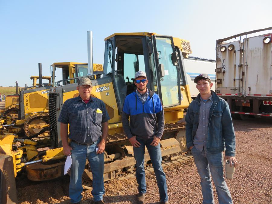 Looking over a John Deere 450J dozer (L-R) are Daniel and Jeremy Byler and Shawn Stutzman.