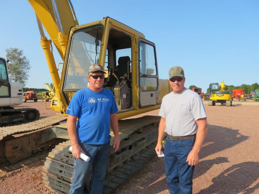 Brothers Ambrose (L) and Joe Lisowe plan to place a bid on this John Deere 590D excavator.