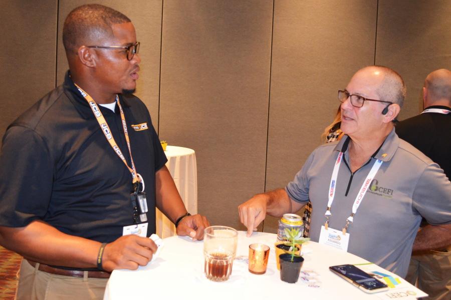 Briggs JCB representative Darius Prentice (L) talks about creative equipment financing plans and ideas with Eduardo Sobrino of Commercial Equipment Finance Inc. (CEFI), Coral Gables, Fla.
