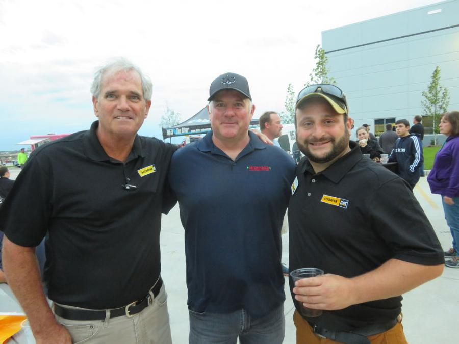 John Loftus (L) and Andrew Izzo (R), both of Altorfer Cat, welcome Coleman McDonagh, president of McDonagh Demolition, to the open house.