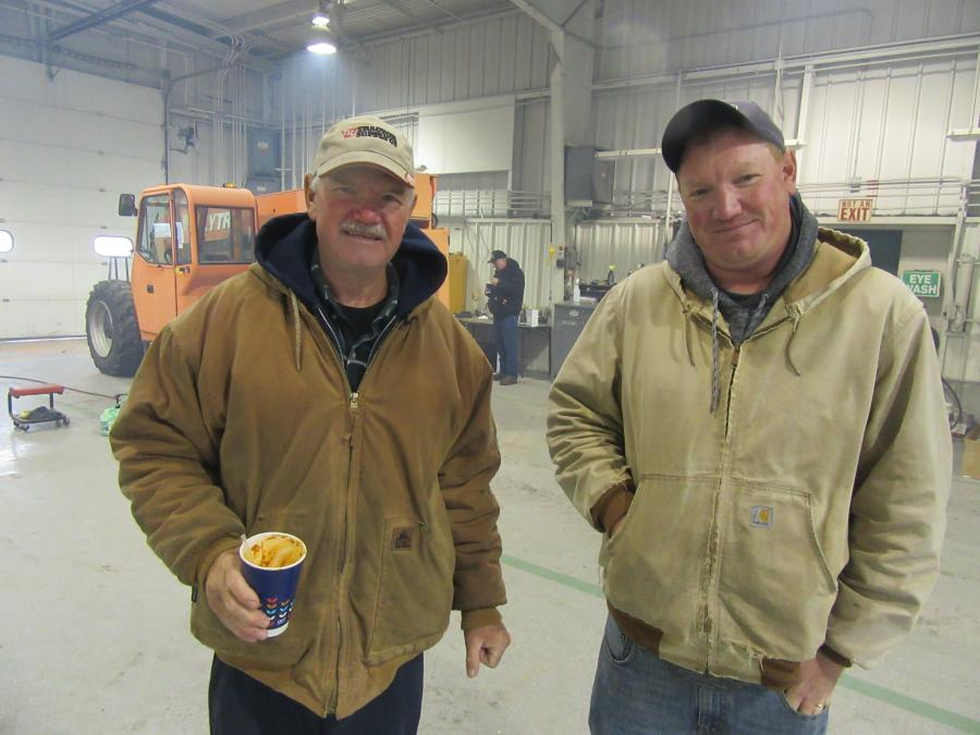 Dave (L) and Dean Schroeder of Schroeder Farms found a dry spot in the Yoder & Frey warehouse to wait for items they were interested in to come up for bid.