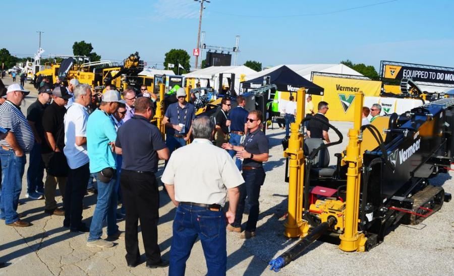 Vermeer Corporation's Peyton Boyle (R) draws a crowd as he goes over features of some of the many Vermeer products in his company's exhibit area.