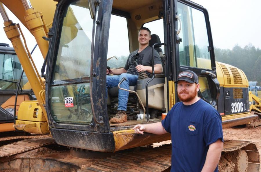 Ryan Hunter (L) and Truett Nichelson, equipment enthusiasts based in Atlanta, Ga., are looking to possibly snag a weekend auction bargain, maybe on this Cat 320CL excavator.