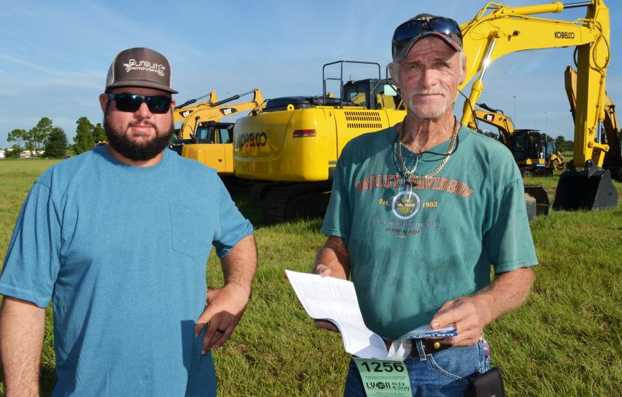 Madison King (L), an independent contractor based in Wildwood, Fla., and Jamie Clevinger, of HMK Hauling, Wildwood, Fla., look over information in the auction catalogue before machine inspections.