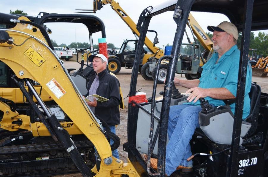 Test operating some of the Cat mini-excavators about to go on the auction block are Chuck Zdenek (L), Zdenek Properties, and Bill Davis, Davis Construction, both located in Quitman, Miss.
