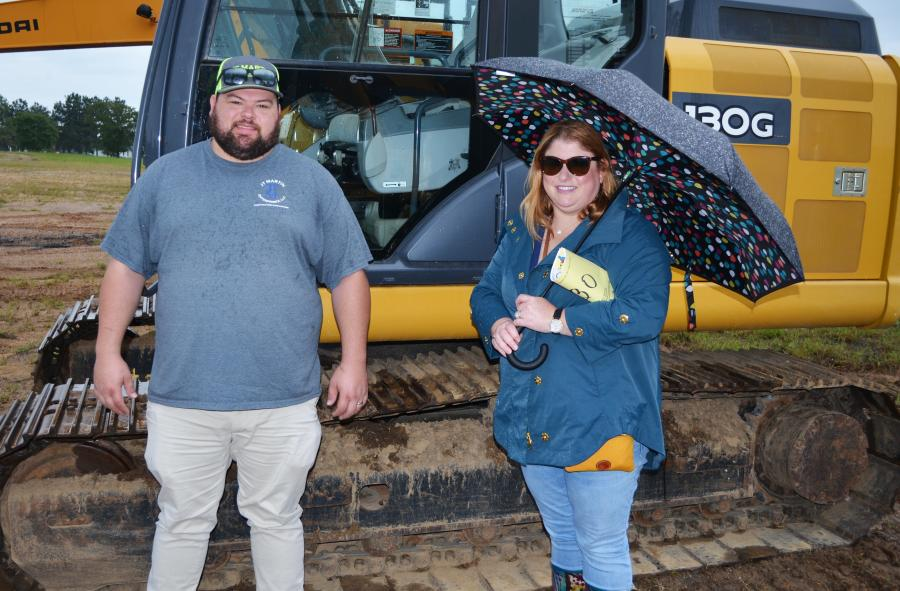 Dodging a few rain drops to look over and test operate some of the machines in the auction line-up are the husband and wife team of Timothy and Jessie Martin, owners of JT Martin Enterprises, Ocean Springs, Miss.