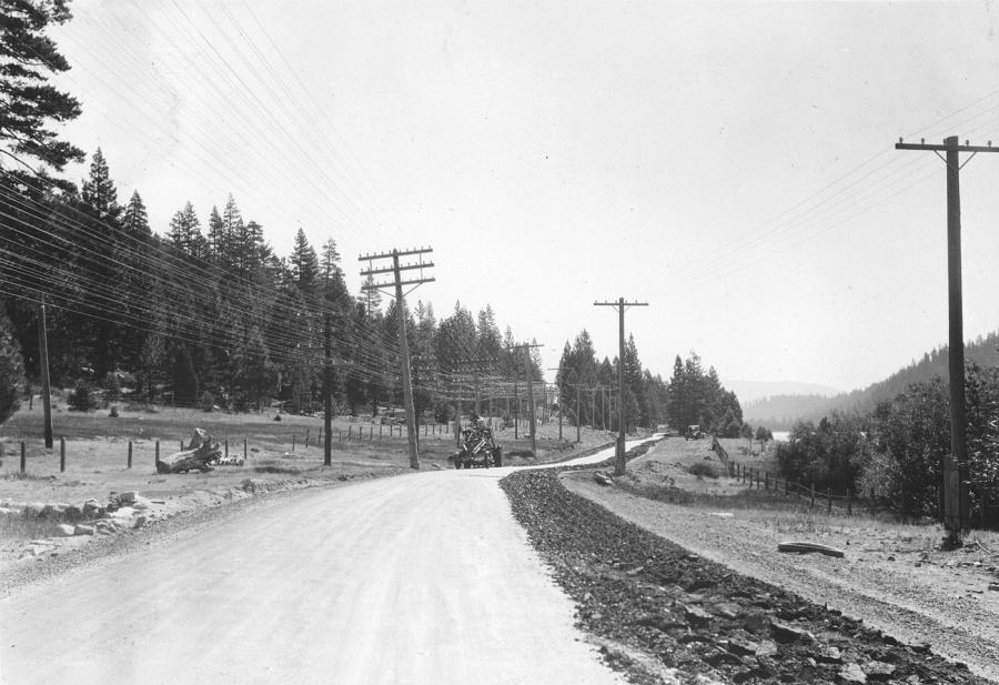 A machine reprocesses the oil mulch roadbed, near Donner Lake, CA. (Photo courtesy Lincoln Highway Collection, Special Collections Library, U. of Michigan)