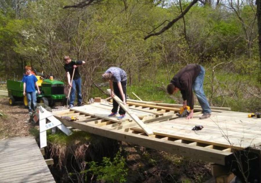 Image courtesy of the Iowa City Press-Citizen.  Jace, a 15-year-old Boy Scout out of Troop 212, got the idea to build the bridge early this year because members of his troop had built bridges for Hickory Hill before.